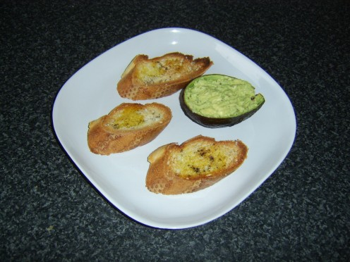 Guacamole is served in an avocado skin shell with bruschetta