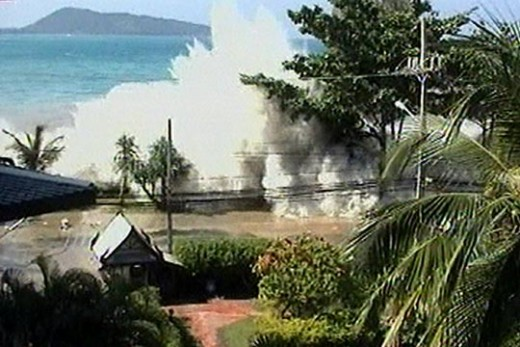 A camera captures the moment the Boxing Day 2004 tsunami batters the coastline of a country in the Indian Ocean. Most residents had already fled when the wave arrived