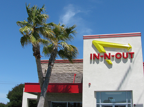 """""""In-N-Out"""" Burger sign, with trademark """"crossed palm trees"""" in front."""