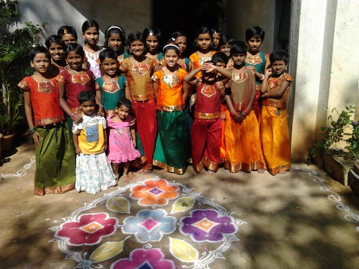 Children at Sharaya Childrens' Home wearing traditional silk langas after bath posing in front of the rangoli in their front courtyard before going to the temple next door to offer pooja on Dasara(Vijayadashmi) day.
