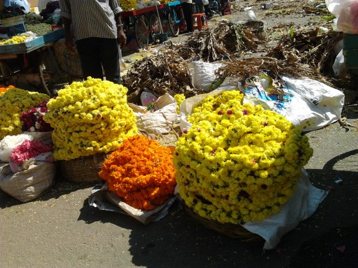 Bundles of fresh, brightly colored chrysanthemums and marigolds.
