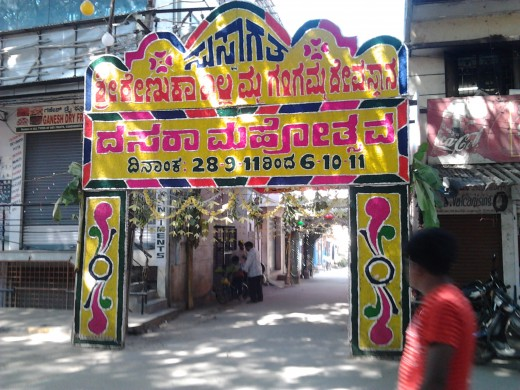 An entrance to a temple adorned with bunting decorated with letters and symbols entirely with colored flowers. It says WELCOME for Dasara celebrations in Kannada(local) language. The street behind it is adorned with floral rows and lights.
