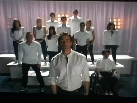 In a true Glee episode ending, Will takes center stage with his club backing him up to sing about his feelings for Emma.