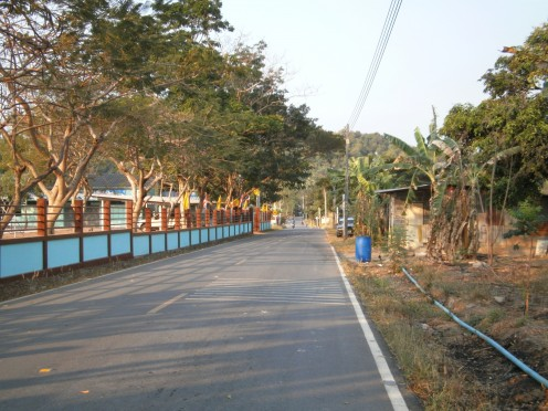 The road into the village with the School on the left and Mr Grumpy Dogs' abode on the right (near the bin)