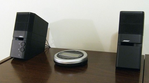 """Photograph of Bose MediaMate computer speakers with a Bose """"Triport CD Music System"""" compact disc player."""