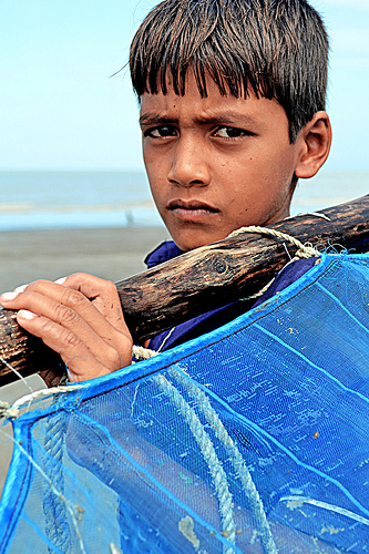 A young local boy with the characteristic and unique local blue fishing net