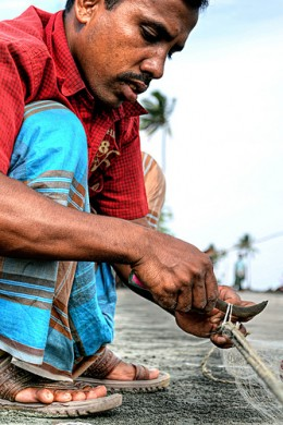 A local fisherman working on his fishing net