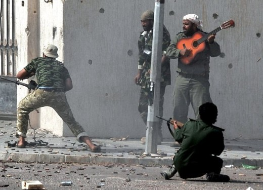 While his comrades spray bullets from their machine guns, this rebel soldier puts up a brave fight in Libya - with a guitar