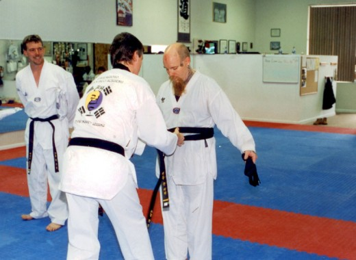 John receiving his black belt in karate.