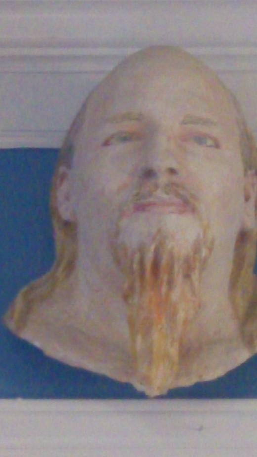 A sculpted bust of John hangs above the door at Little John's Tattoo.