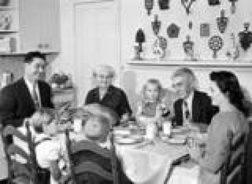 THE TYPICAL, VINTAGE AMERICAN FAMILY OF THE 50'S SITTING TOGETHER--EATING, LAUGHING, SHARING STORIES.