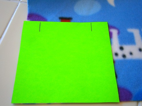 LIne green card on one corner and cut fabric along edges.