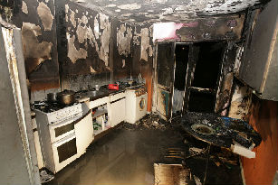 Aftermath of a kitchen fire. Note the appliances are still white, just above them you can see a clear line on the wall. Above that line is where the superheated gasses and smoke are during a fire, near the floor is clear air as discussed in the text