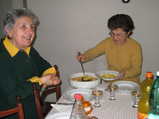 Cousins, Ana and Maria, serving fresh homemade tortellini in brodo (tortellini soup), for our dinner.