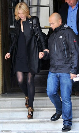 Gwyneth Paltrow clutches her bodyguard to avoid any embarrassing tumbles on the steps