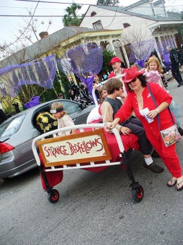 """Strange Bedfellows"". New Orleans Mardi Gras revelers pushing bed in neighborhood street"