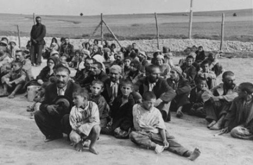 """A group of Gypsy prisoners, awaiting instructions from their German captors, sit in an open area near the fence in the Belzec concentration camp."""