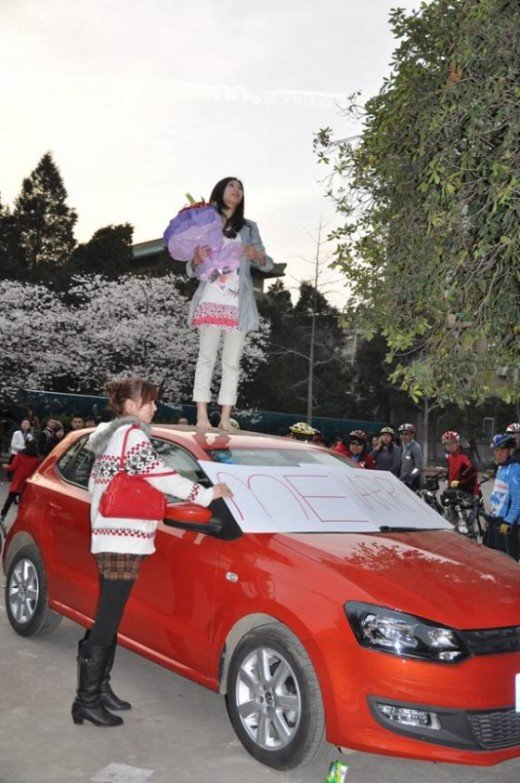 MARRIAGE PROPOSALS CAN GO BOTH WAYS. THIS CHINESE GIRL IS PROPOSING TO HER FIANCE' FROM ATOP HER CAR. WHAT LOVE! WHAT DEVOTION!