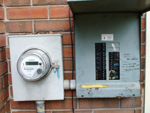 The electricity passes through the electric meter before passing into the circuit breaker panel.