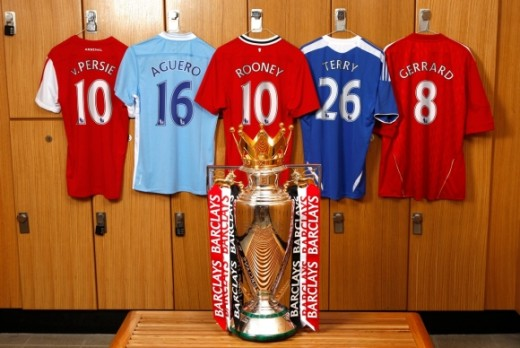 Some club shirts lined up behind the Premier League trophy