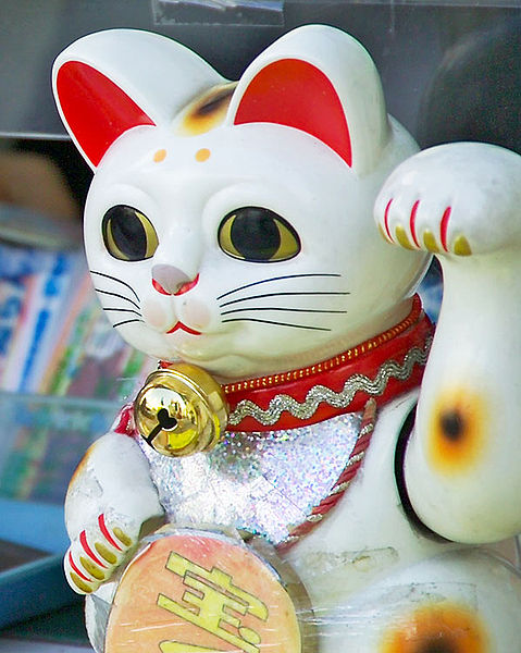 A maneki-neko statue in Tokyo beckoning passers-by to come and play the lottery.