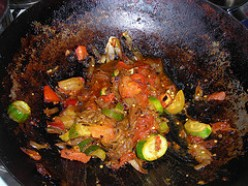 Onion, eggplant, courgette and tomatoes frying in a pan