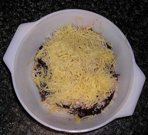 Stuffed eggplant sprinkled with breadcrumbs and grated cheese, ready to be baked for 20 minutes