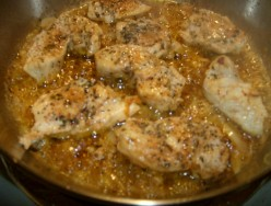Chicken breast pieces browing with herbs and other seasonings.