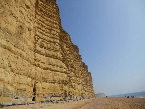 Golden sandstone cliffs tower above the shingle beach, contrasting with the clear blue sky and the sea. West Dorset, March 2011.