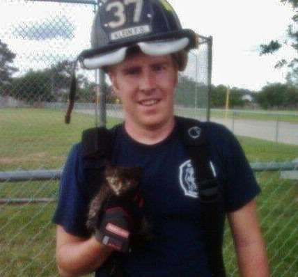 Volunteer fireman rescues a kitten.