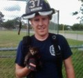 Volunteer fireman rescues a kitten.