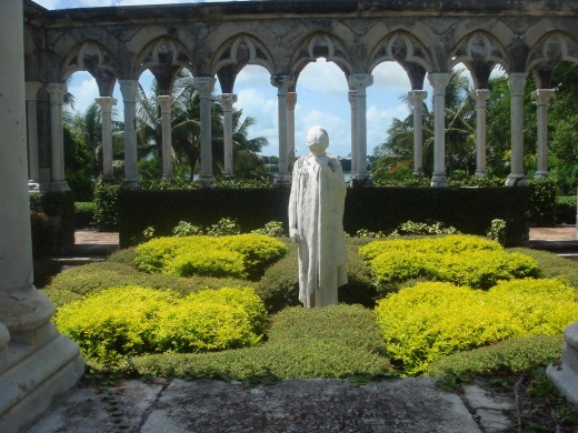 Front view of the statue with greenery in the center of the stone structure of the Cloisters.