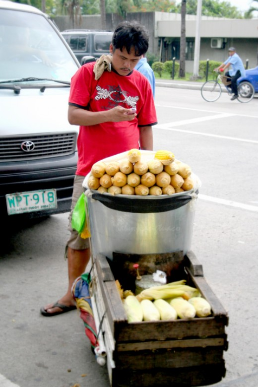 corn vendor texting somebody on his cell phone while waiting for buyers of his goods. Notice the boiled corn is kept hot by a portable stove underneath the big kettle