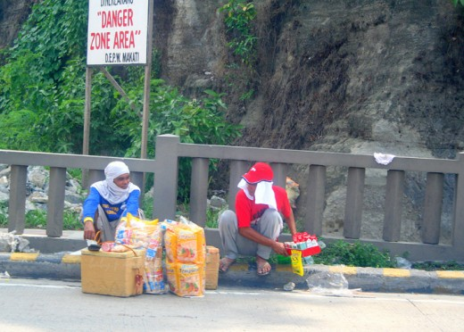 street hawkers taking a rest, unmindful of the danger sign behind them
