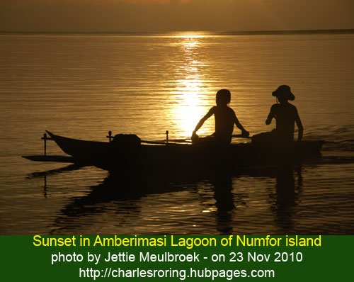 Sunset in in Amberimasi lagoon - the golden light of the sun as reflected on the surface of the water and the silhouette of the boys rowing their canoe at the foreground