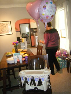 Continue the cupcake theme with birthday decorations on a highchair.