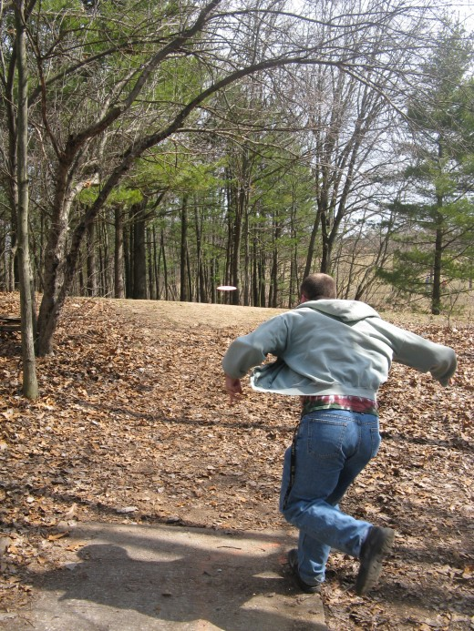 Disc golf drive photo - again the action of the subject's sweatshirt flapping in the win on this one makes it interesting.  Also, being able to see the disc flying through the air adds a bit to the shot.