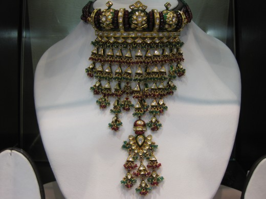 Aadia, a typical Indian pattern of Jaddau Kundan Meena necklace. This gold ornament is studded with flat diamonds.