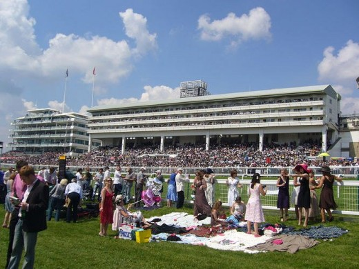 Women lay out picnic blankets next to the track at Epsom