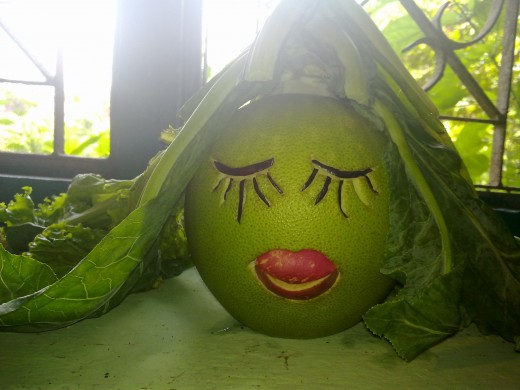 A green pomelo is given cauliflower leaves as headscarf; eyes are made from egg plant peels and lips from apple peels. Now she is a beautiful girl.