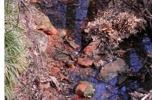 A small drainage creek by the pond.  Its deep azure sky reflection contrasts with Okie red soil and sandstone as I snap the photo from a small bridge.