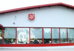 The front of the Salvation Army Family Store Building which faces its own parking lot. The murals are on the long, left side of the building which faces the street.