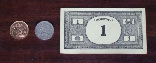 A Victorian gold sovereign, a modern £1 coin and a vintage Monopoly money note, for comparison