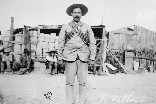 "Francisco ""Pancho"" Villa (1877–1923), Mexican revolutionary general, wearing bandoliers in front of an insurgent camp."