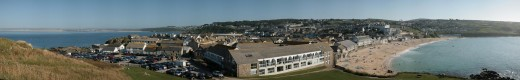 Panoramic view of St Ives including the Island, Porthmeor beach and St Ives Bay to the other side