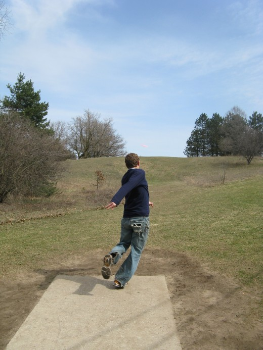 One of the best ways to set up a disc golf drive photo is by finding a good landscape background and having your subject throw multiple drives from the tee pad.