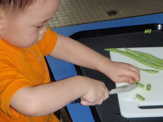 A child slices beans with a knife at a Montessori school: preschool children are taught independence and practical skills at a young age.