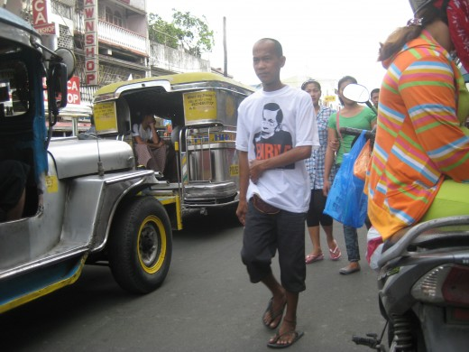 A man walking along with passing jeepneys - most common public utility vehicles in the Philippines