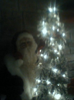 Father Christmas by a glowing tree