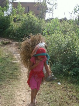 "A young girl walks with a load of paddy on her back and slippers on her hand. ""Why are you not wearing slippers,"" I asked. ""I'm getting late for school and I find bothersome to walk in slippers,"" she said."